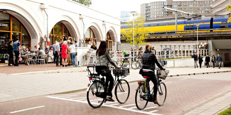 Vrouwen fietsen voorbij Hofbogen waar mensen staan.